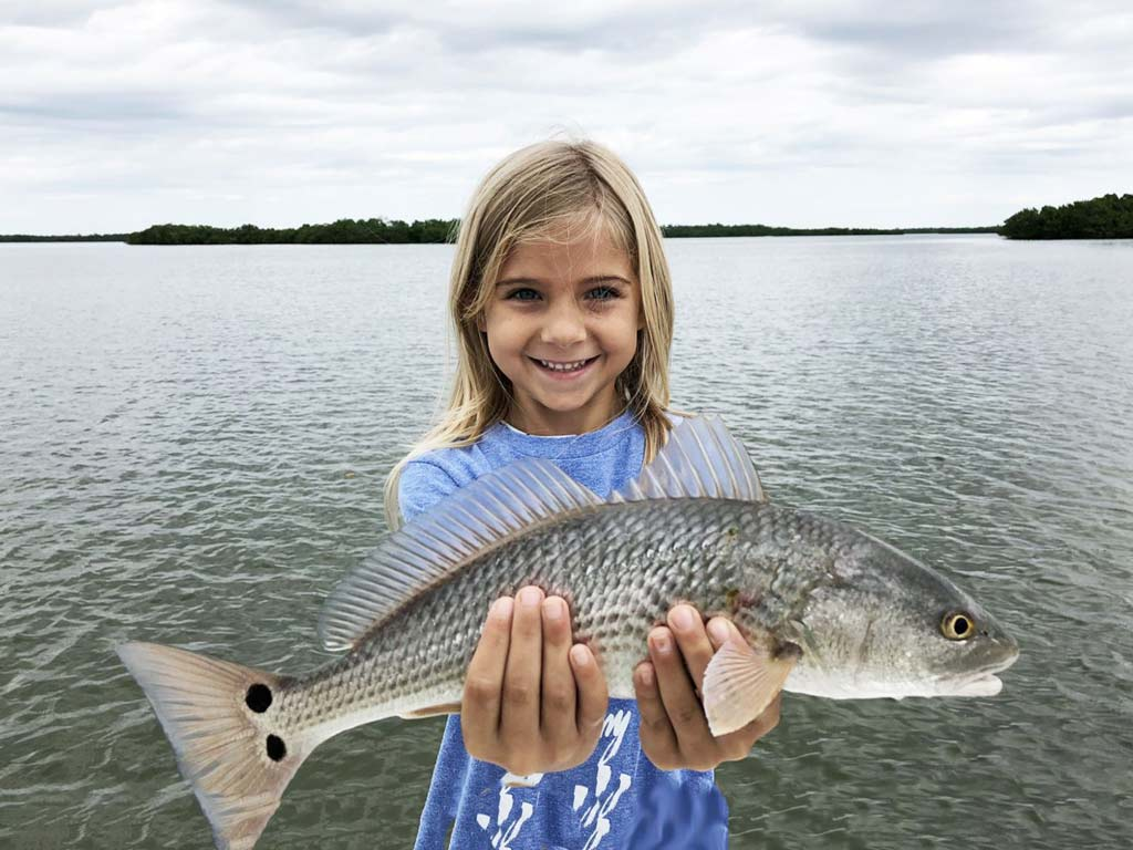 A young girl holding a Redfish, caught while fishing in the Bonita Springs area.