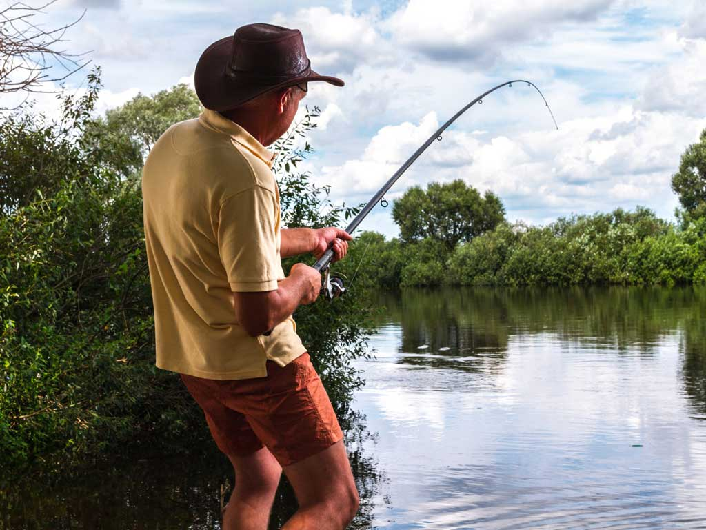 An angler reeling in a fish from shore.