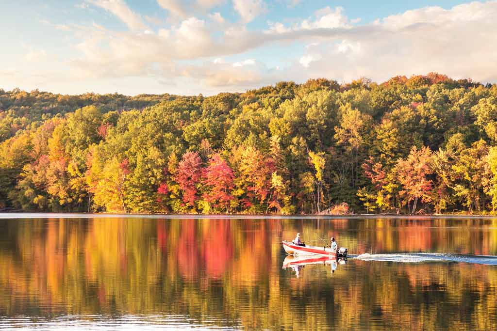 Two anglers on a fishing boat in the middle of a lake, surrounded by autumn foliage