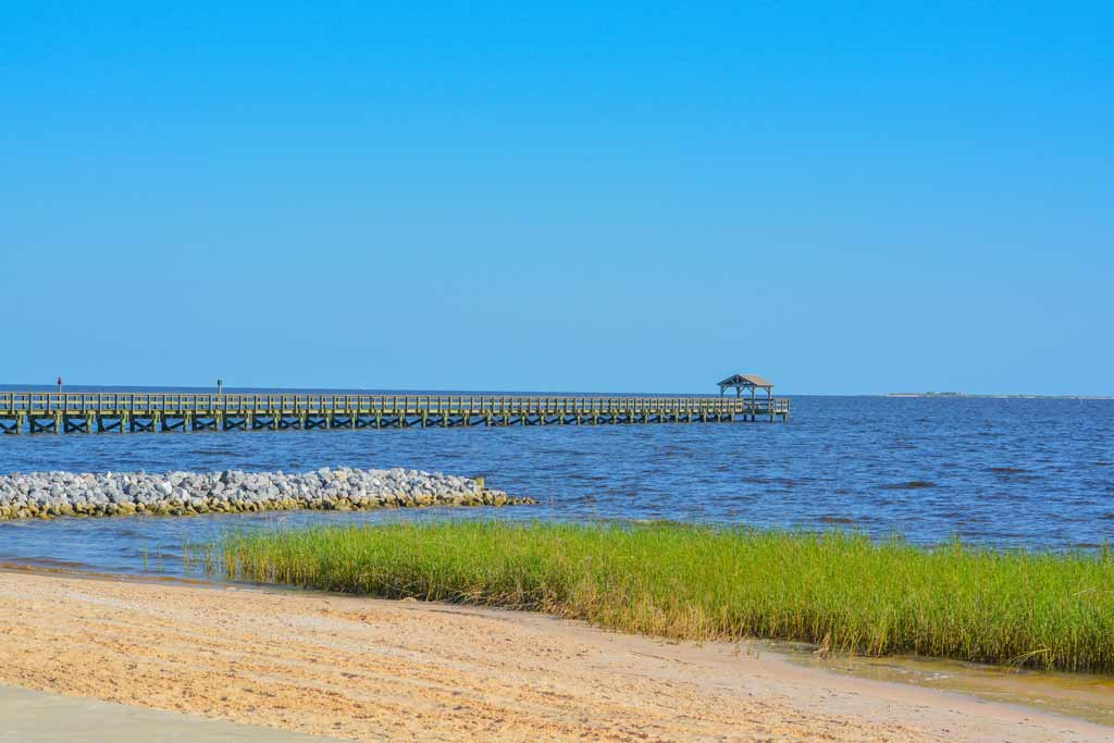 A long fishing pier in Biloxi in the distance, with water, a beach, and blue skies