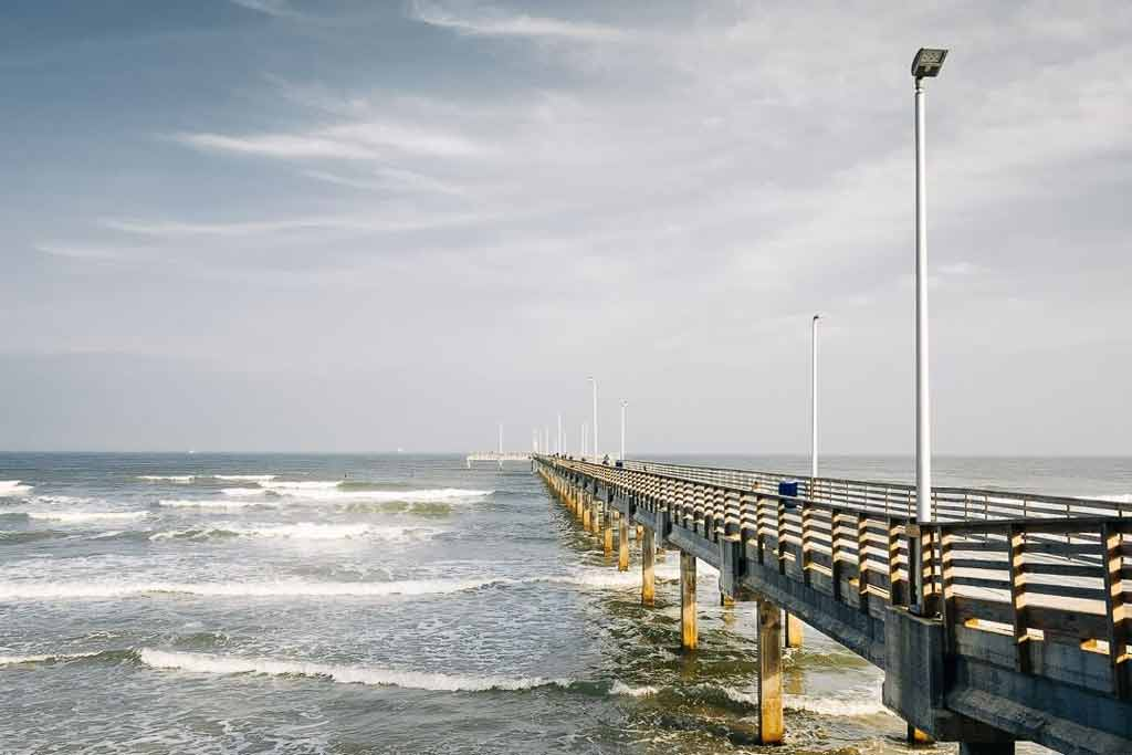 A pier in Corpus Christi with small waves in the surrounding water