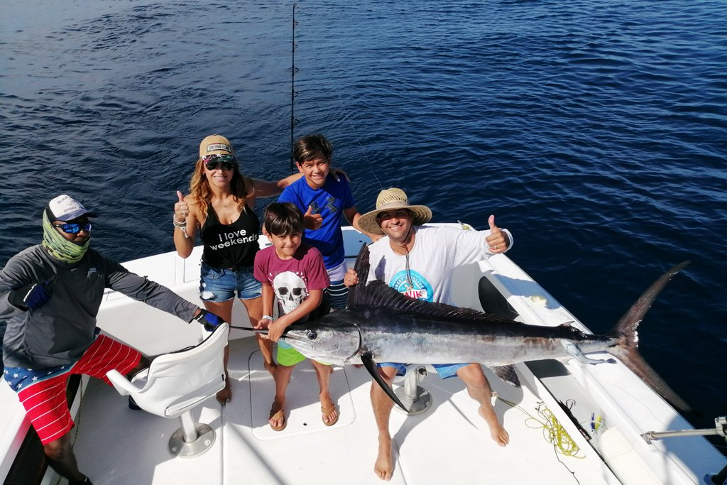 A group of anglers stand aboard a deep sea fishing charter holding a large Marlin