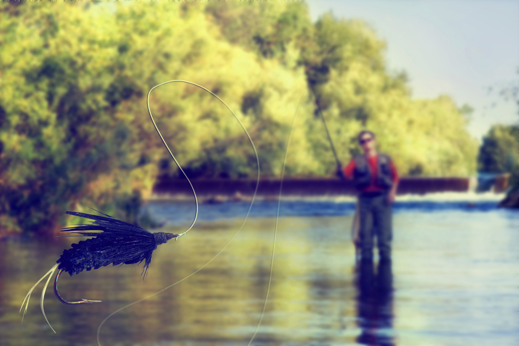 A man casts a large fishing fly towards the camera on a sunny day while standing in water