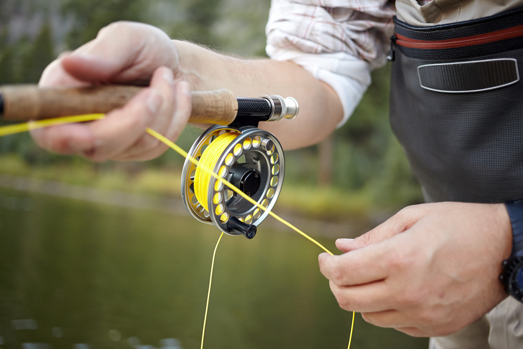 A close-up of a fly fisherman's hands as he pulls line on his reel