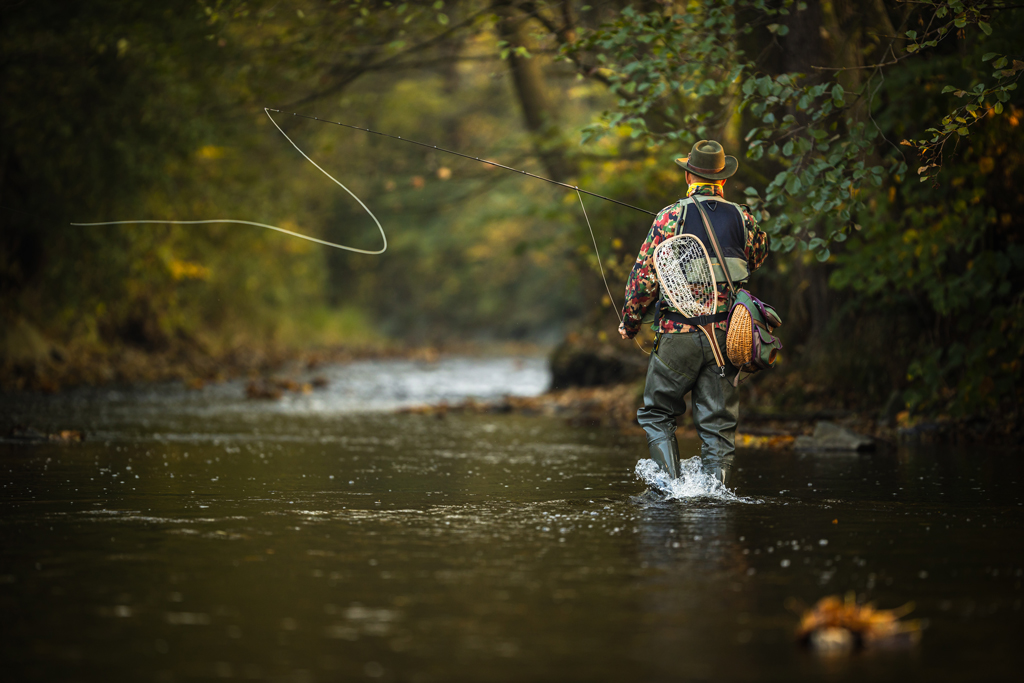 A man stands in a river surrounded by greenery as he makes a cast on the fly