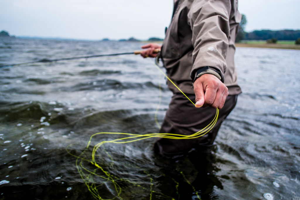 An image of a fly fisherman from the neck down standing waist-deep in water and pulling line towards him