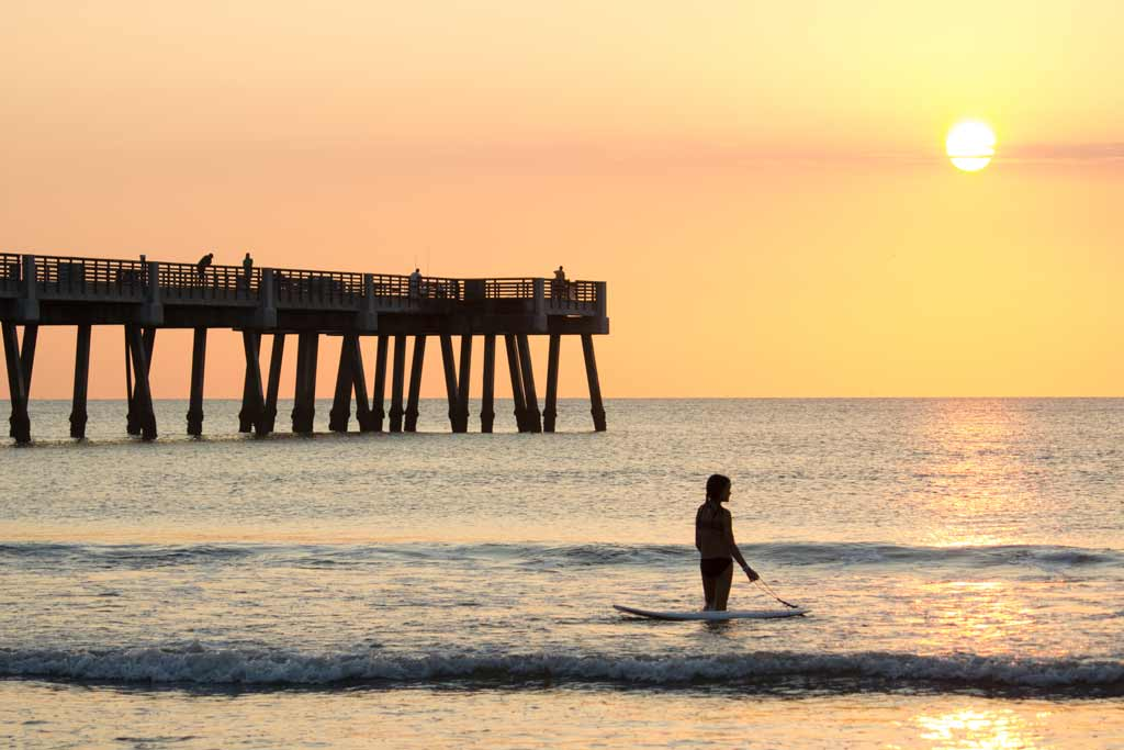 A woman with her paddleboard in the surf on a Jacksonville beach, with a pier in the background