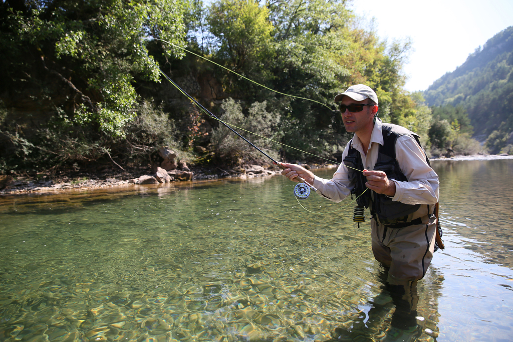 A man casts a line in a clear river on the fly