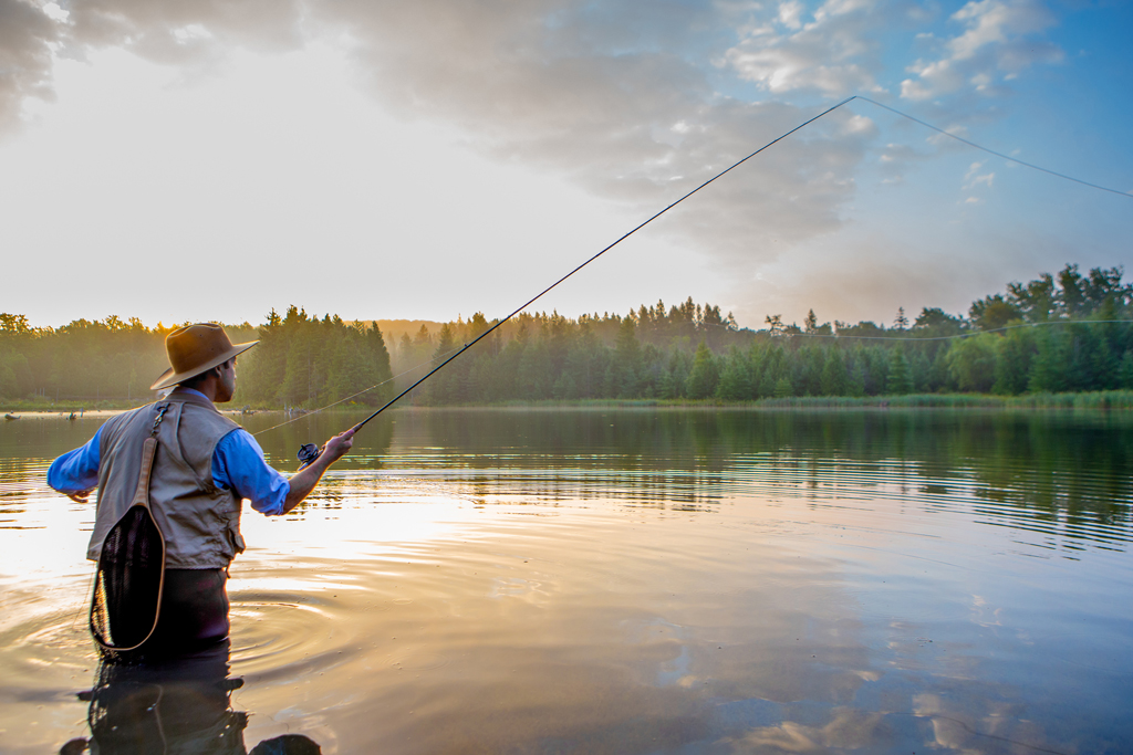 A man fly fishes at sunset after wading into a waterway