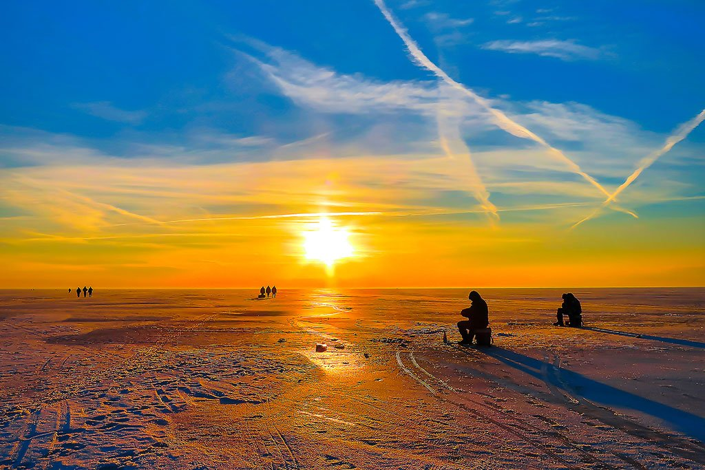 Two anglers on the ice cast into their holes with the sunrise in the background