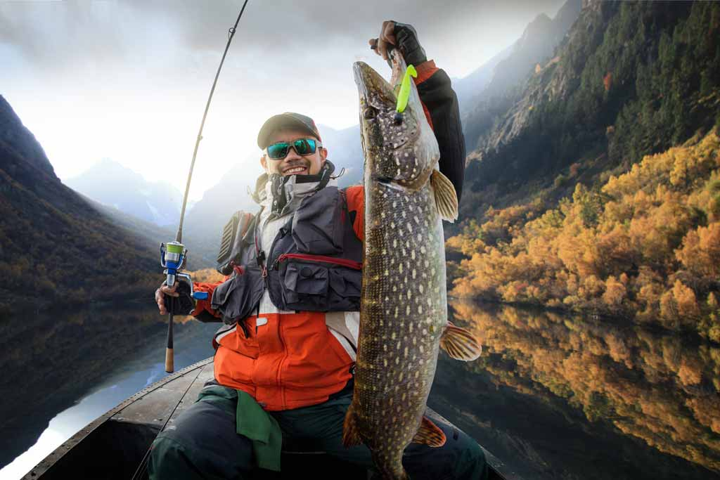 A fisherman on a boat, holding a Northern Pike and a fishing rod, with cloudy skies and mountains in the background