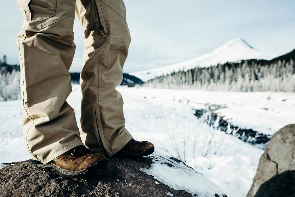 A closeup of man's waterproof pants while standing on a rock with snowy landscape in the background