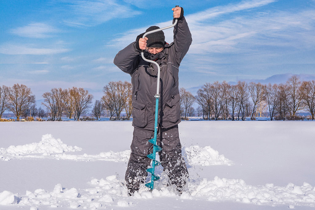 A man drills a hole into the ice using an auger, ready for an ice fishing trip