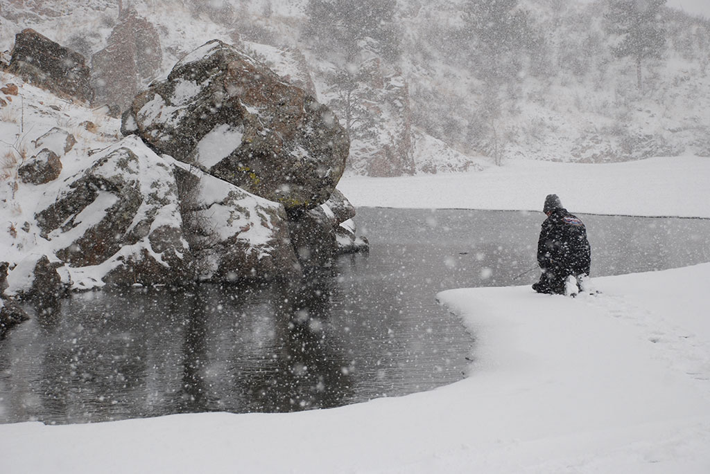 A lone angler casts a line near Mullet Lake, MI, during a blizzard