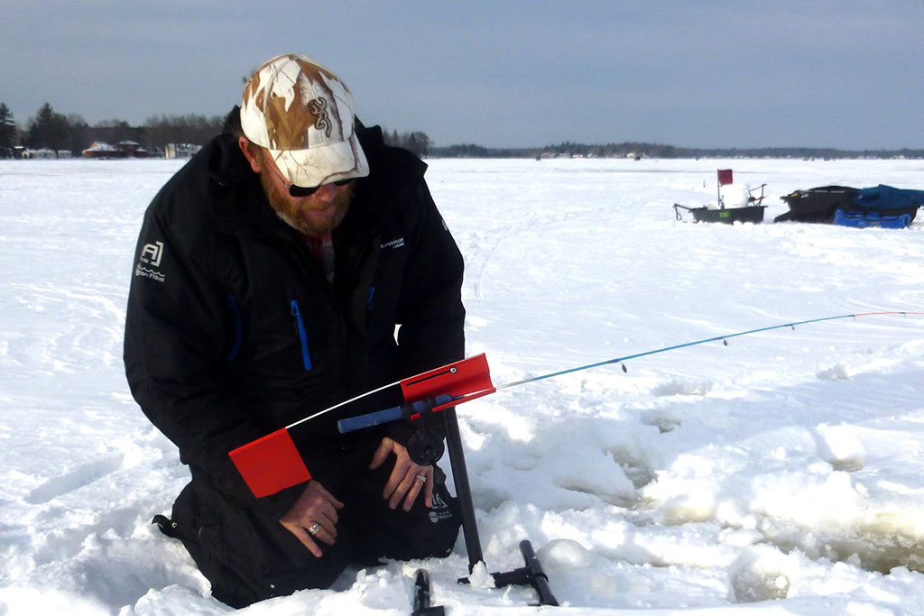 An angler sets up his rig on the ice before ice fishing