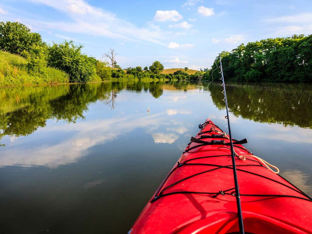 A photo showing the view from a kayak with a fishing pole visible.