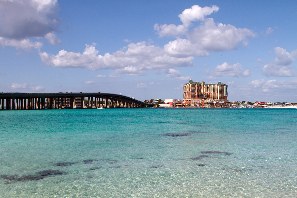 A view of Destin with the bridge and cityscape in the distance and the water in the foreground