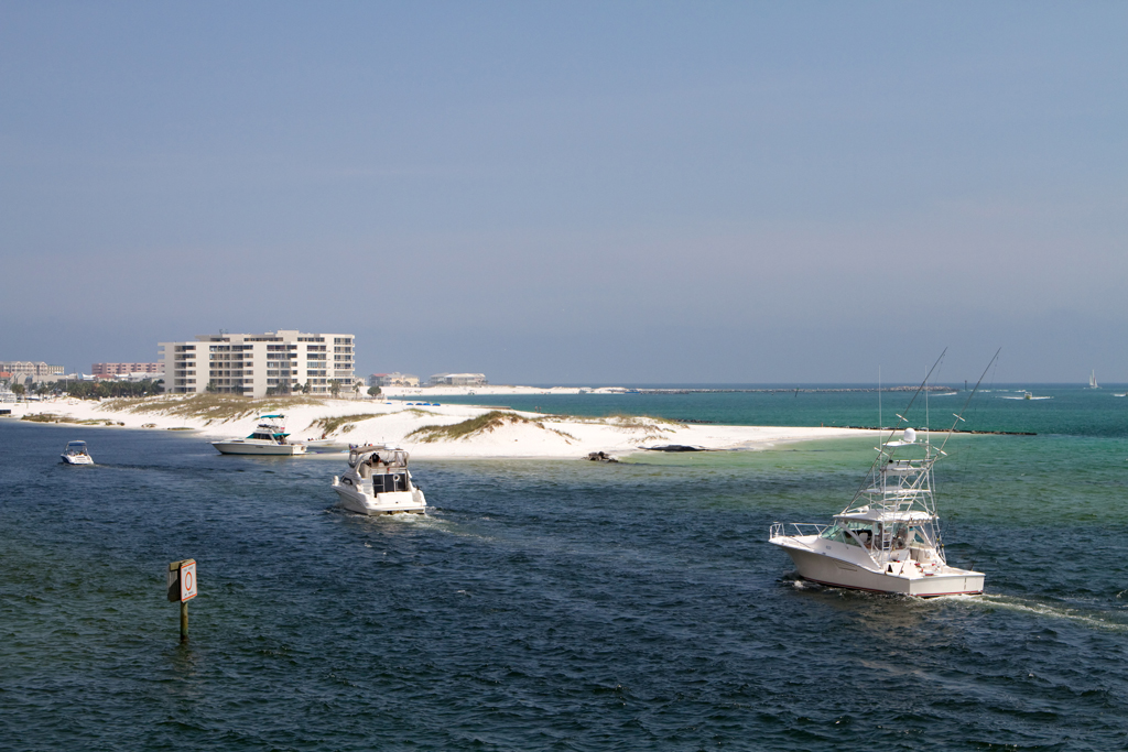 A view of charter boats in Destin traveling across the water towards the harbor