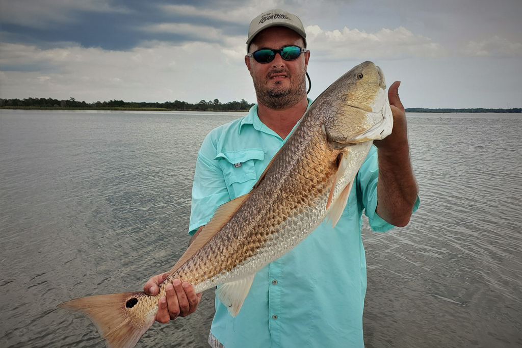 A man holds a large Redfish with the waters of Destin behind him