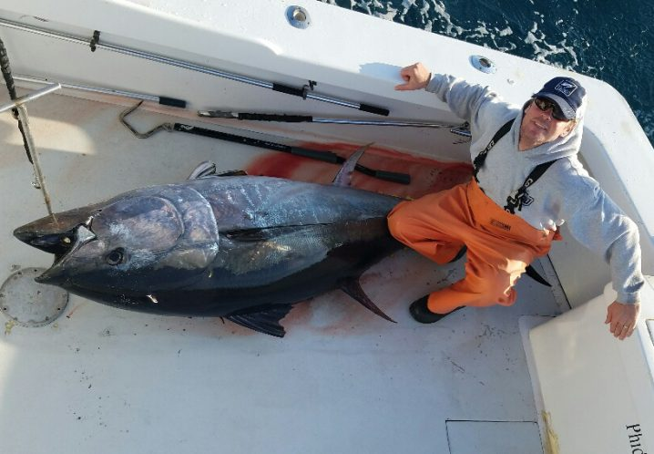An angler in orange waders kneeling by a tuna he caught when giant Bluefin Tuna fishing in the Outer Banks