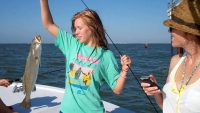 Teenage girl catches Speckled Trout on a Texas fishing charter