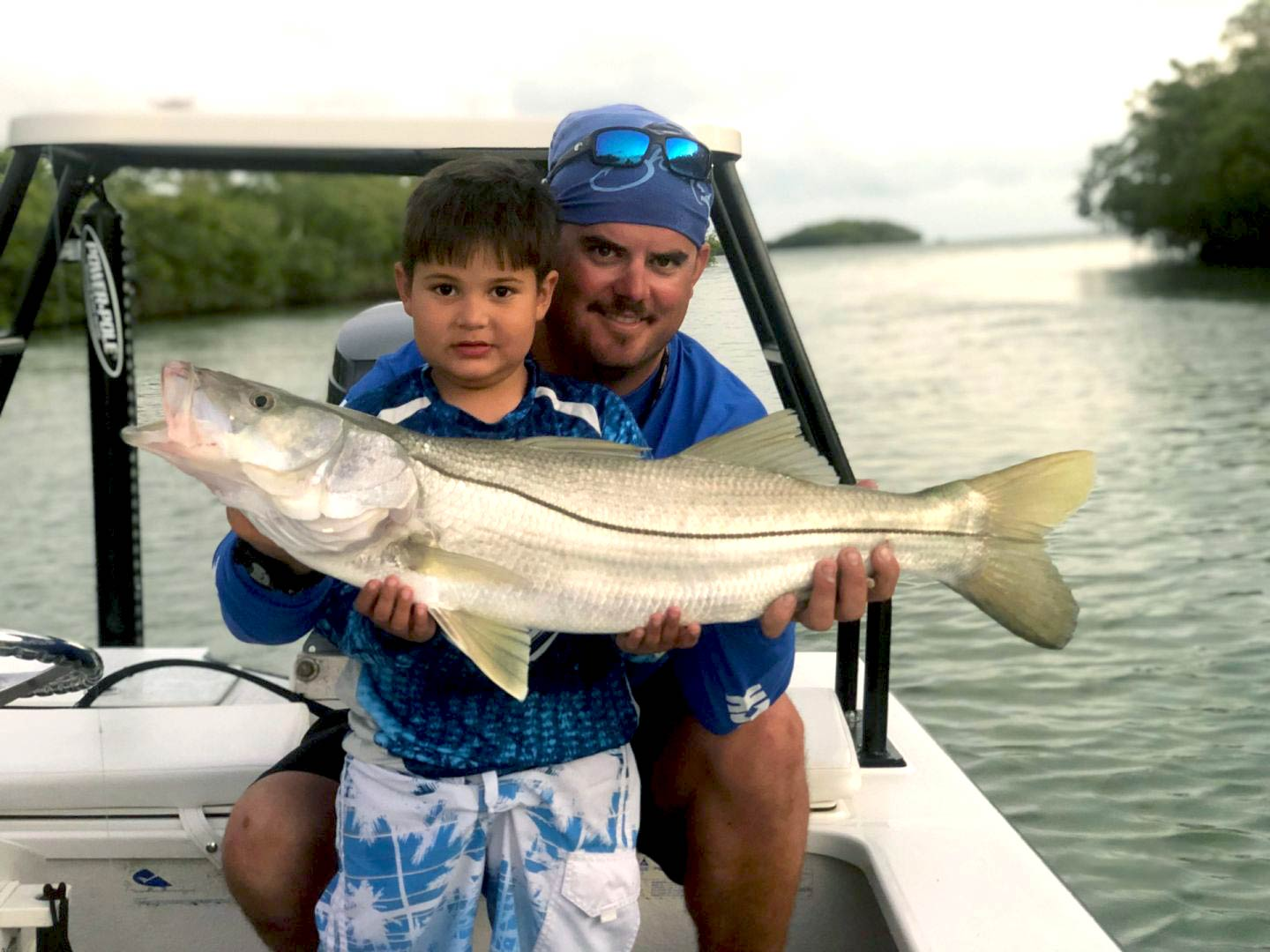 A man and a child holding a Snook in the wetlands of the Everglades, Florida