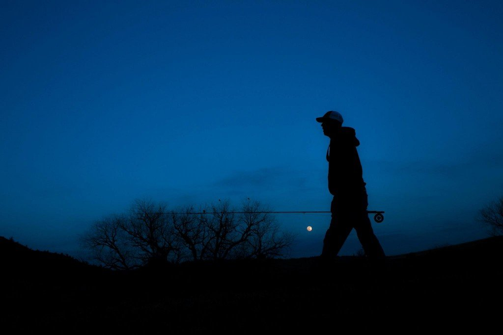 An man walking at night with a fishing rod in his hand
