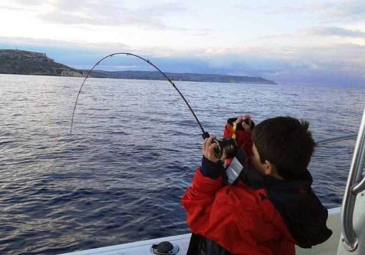 A young angler in a red jacket fighting a fish with his fishing rod bent over the side of a boat.