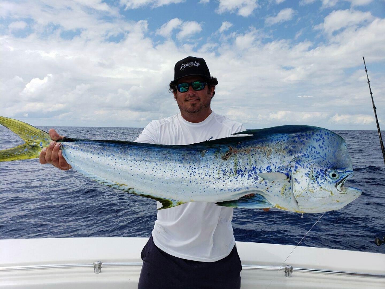 A man holding a Mahi Mahi on a boat in Florida