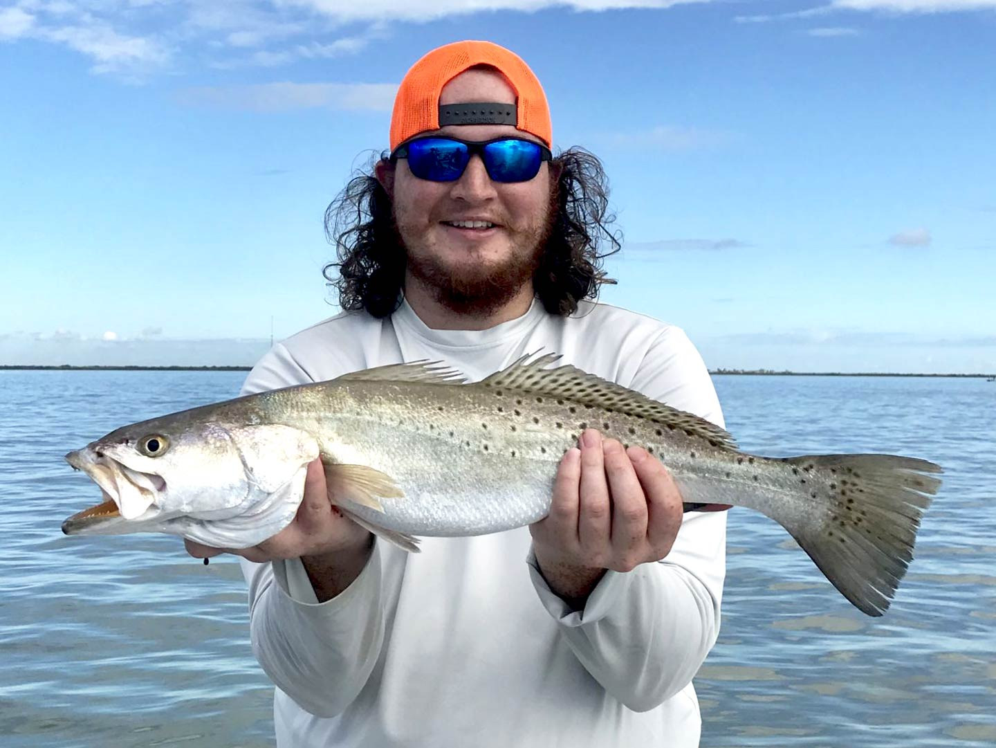 A man holding a Speckled Trout on a boat
