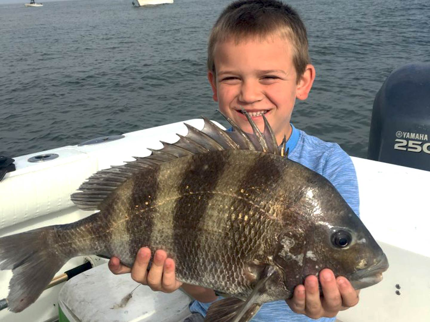 A happy kid holding a Sheepshead on a boat