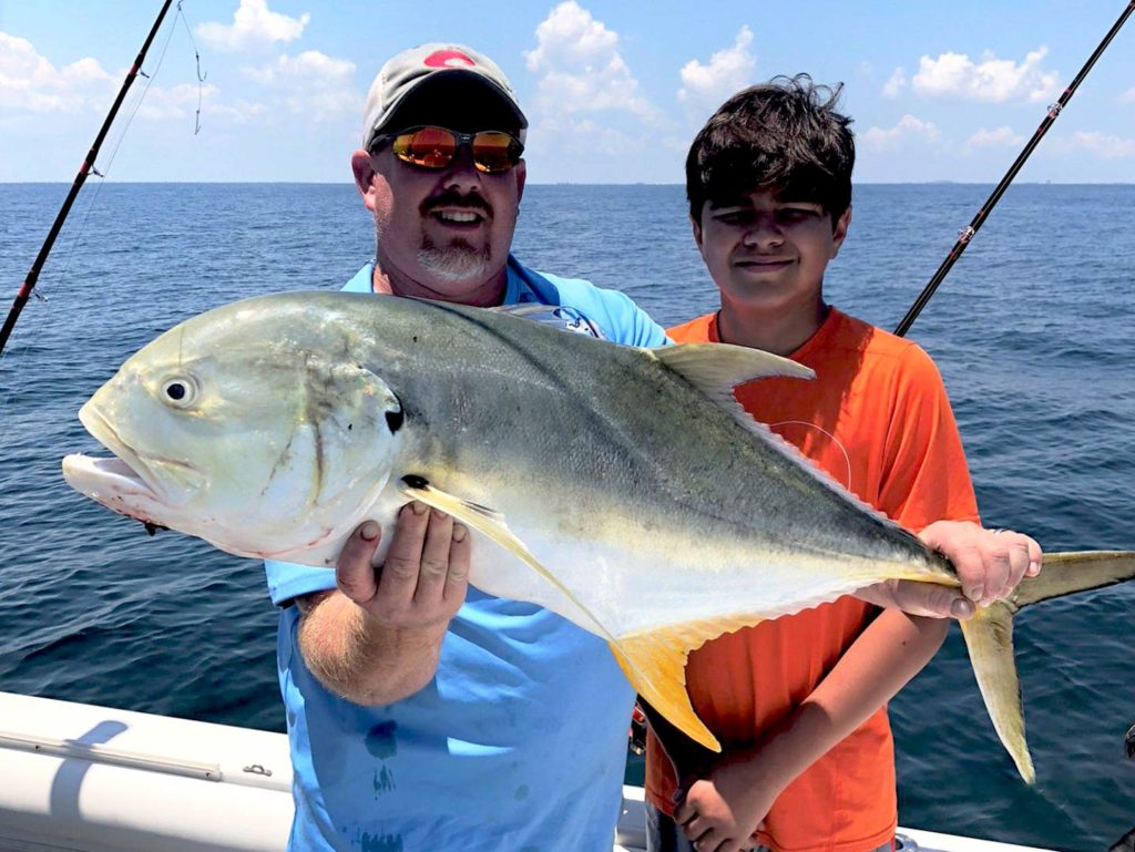 A man and a boy holding a Jack Crevalle on a boat