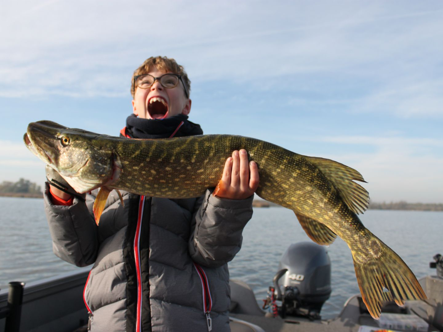 A happy kid smiling, holding a big Pike on a boat