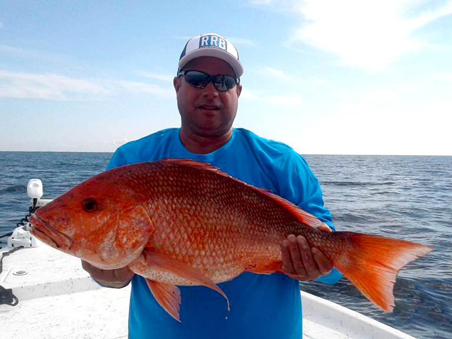 A man holding a Snapper on a boat in Florida