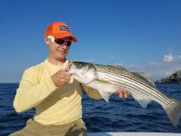 A happy angler in a yellow top holding a Striped Bass