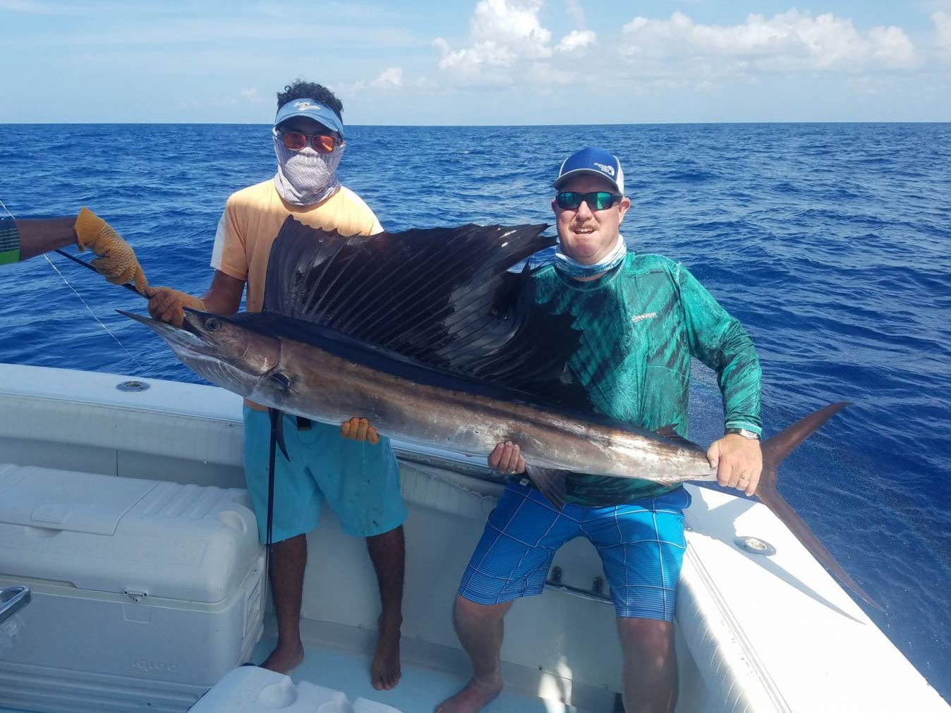 Two anglers standing on a boat holding a massive Sailfish, with water in the background