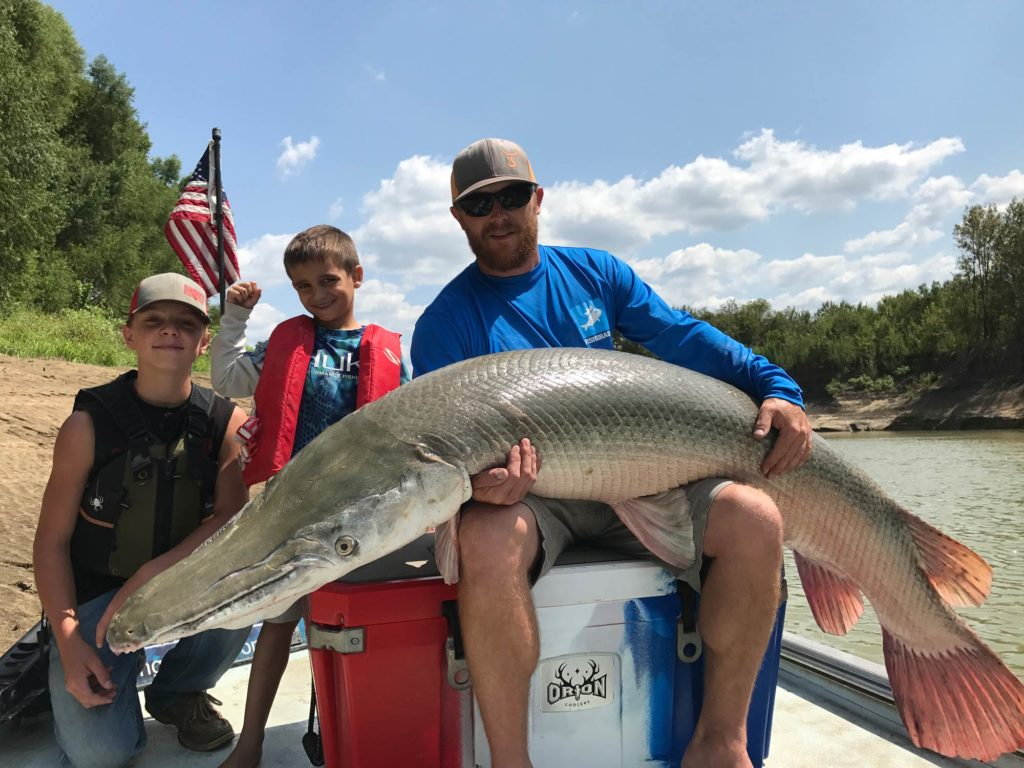 A happy family of anglers sitting on a boat with a Alligator Gar on man's lap