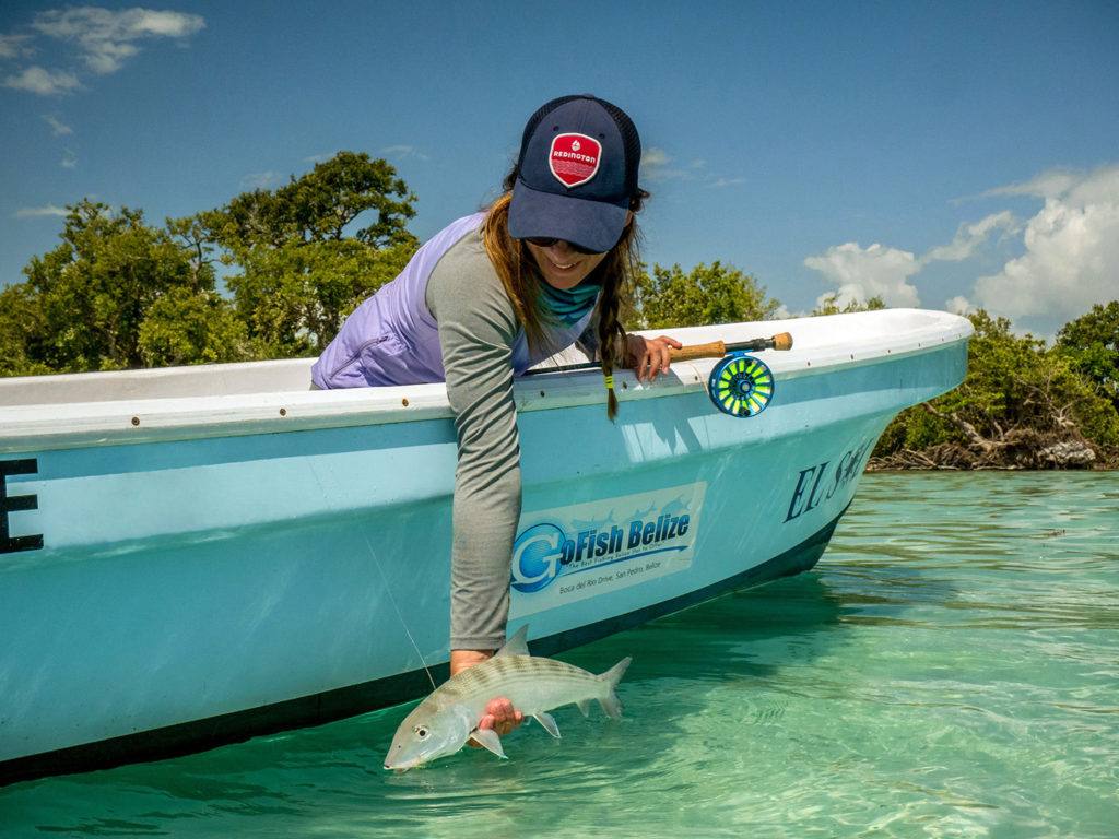A female anglers releasing a Bonefish into clear shallow water from a boat, with green vegetation behind
