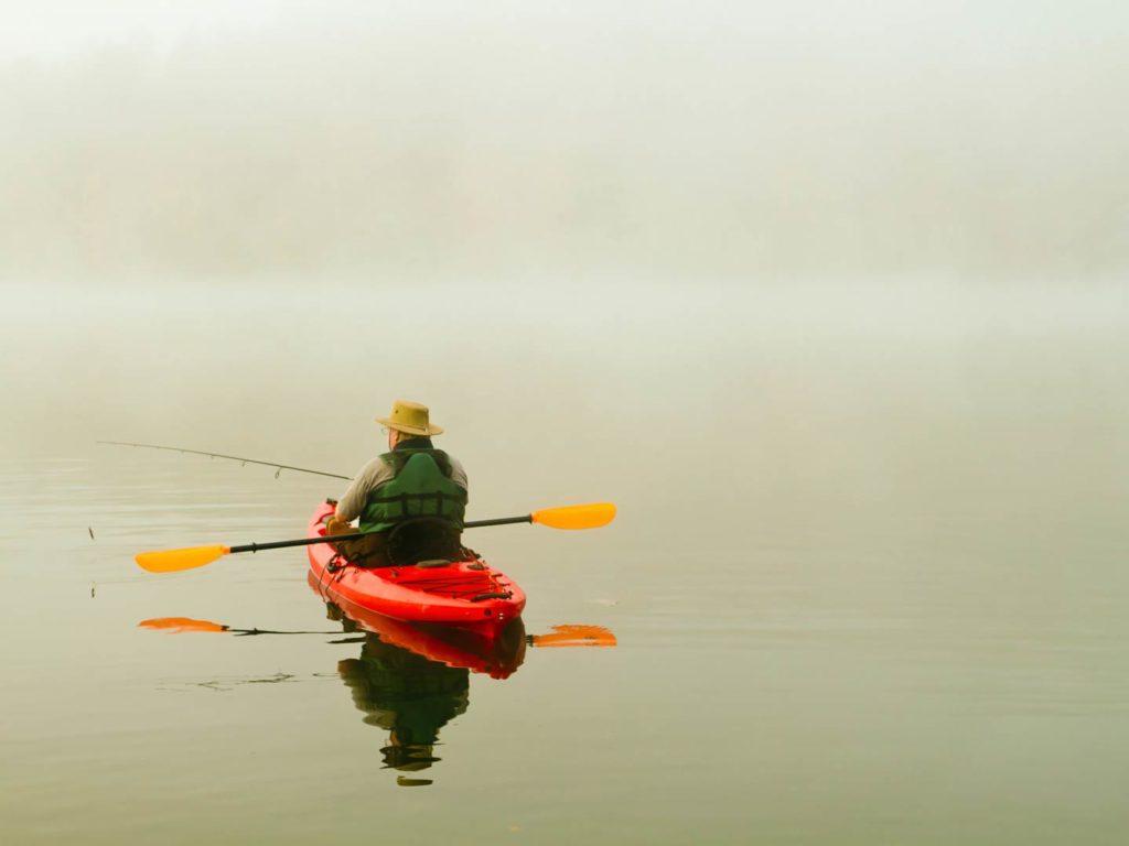 An angler kayak fishing on a lake