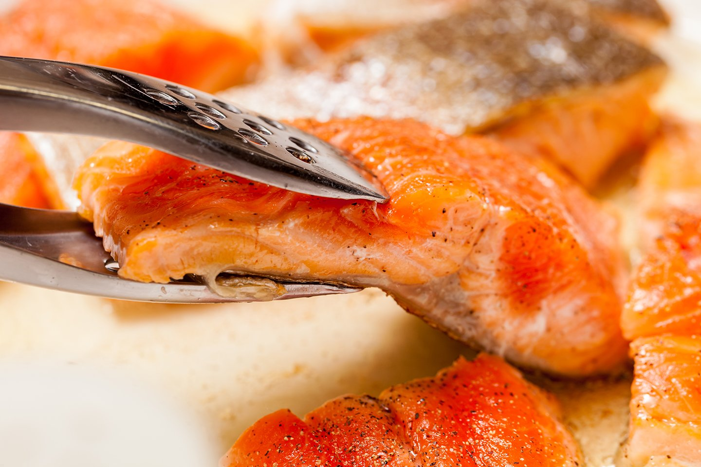 Pieces of grilled Salmon being turned with metal tongs