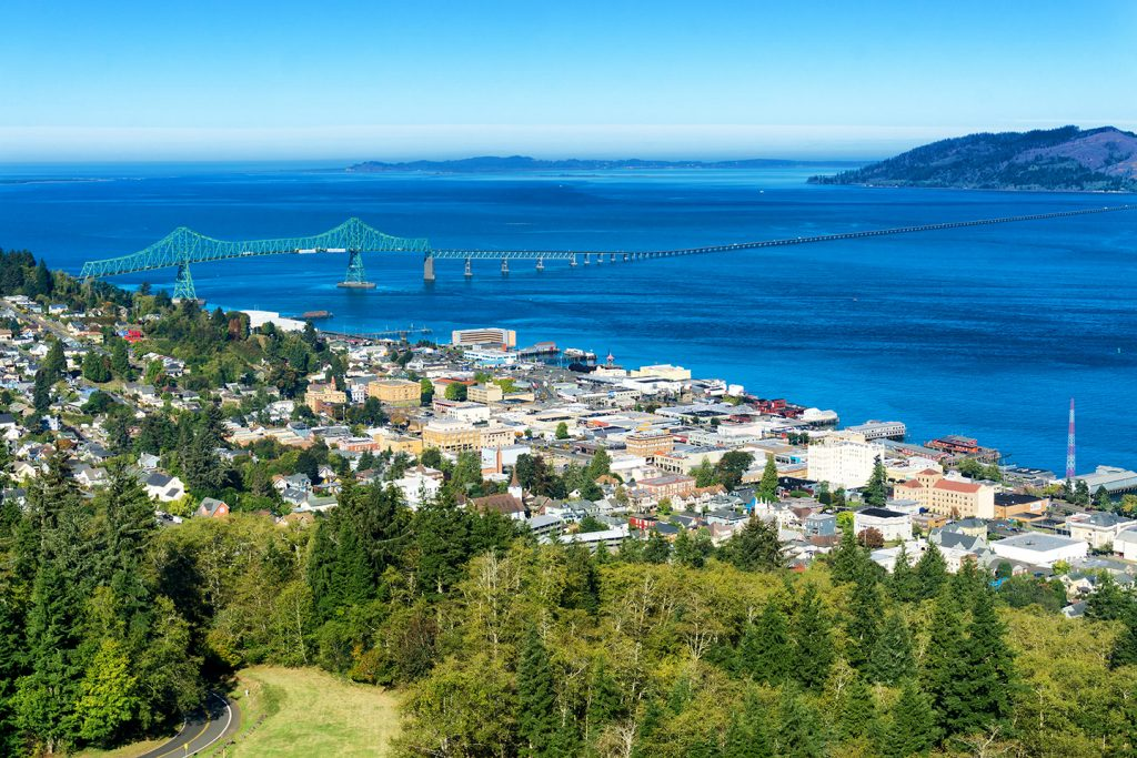 The town of Astoria, Oregon, one of the best Labor Day fishing destinations in the US. Green trees are in the foreground, with white buildings behind and the blue water of the Pacific Ocean in the distance