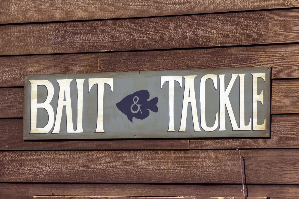 A sign on a wooden wall advertising bait and tackle for sale, with a picture of a Sunfish in the middle