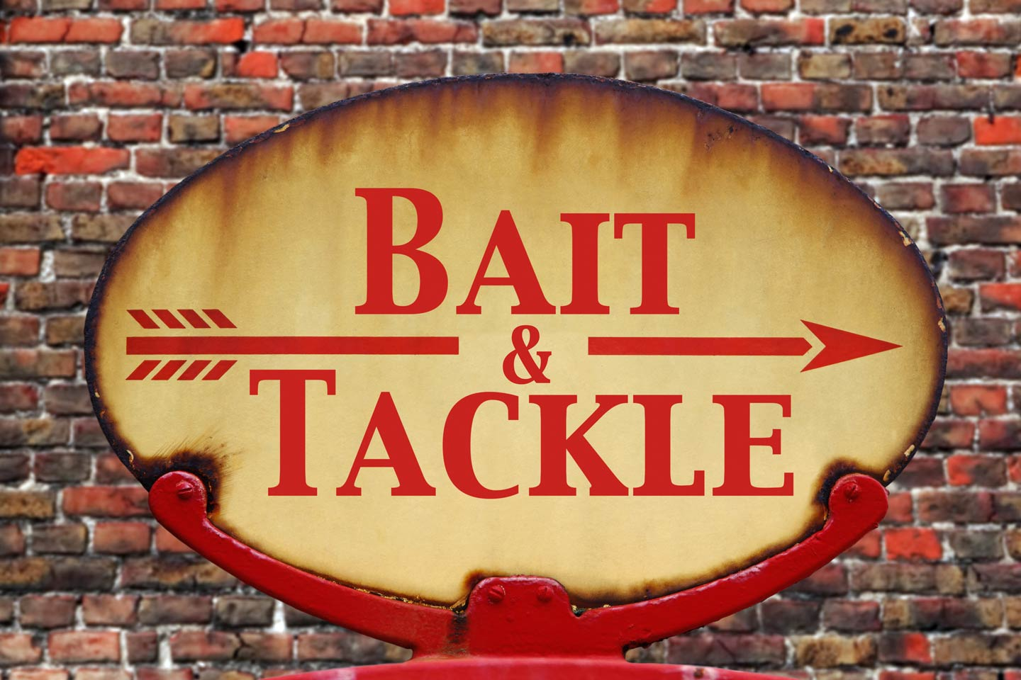 A vintage red and yellow bait and tackle sign against a brick wall.