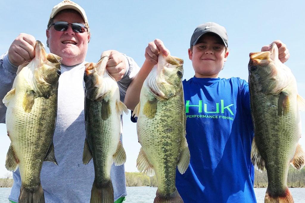 two fishermen holding four Largemouth Bass