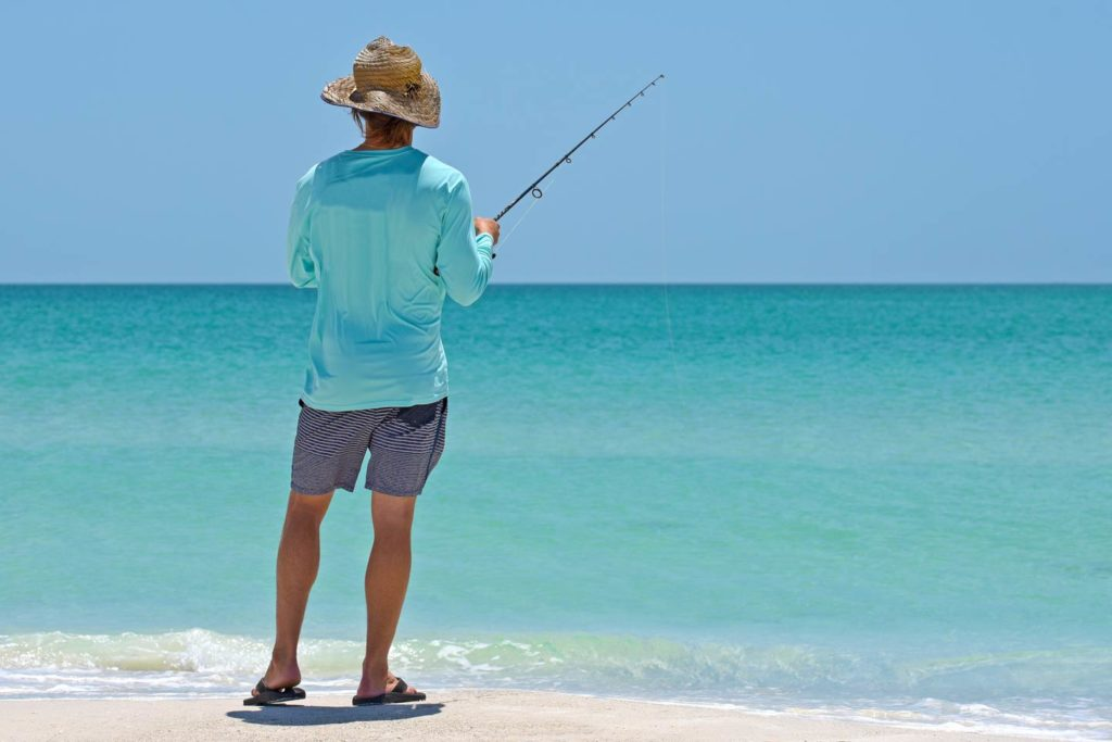 An angler, pictured from behind, fishing from the beach.
