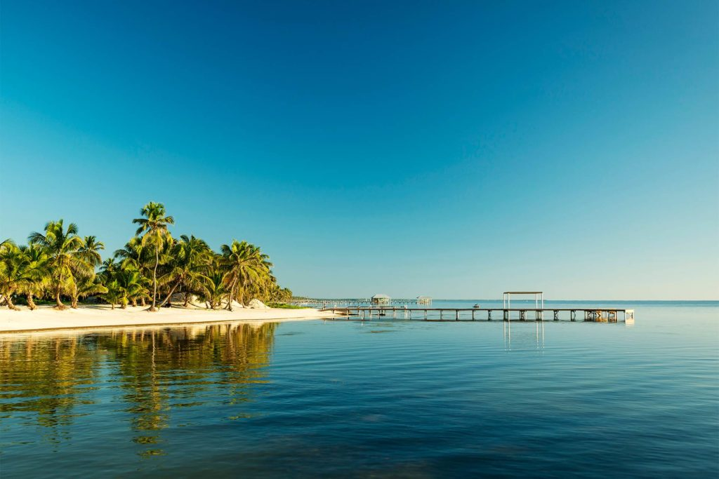 A large pier leads out into the water from a golden beach in Belize