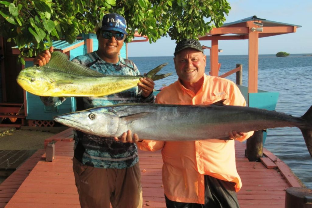 Two anglers hold a Mahi Mahi and Mackerel caught on a Belize fishing trip