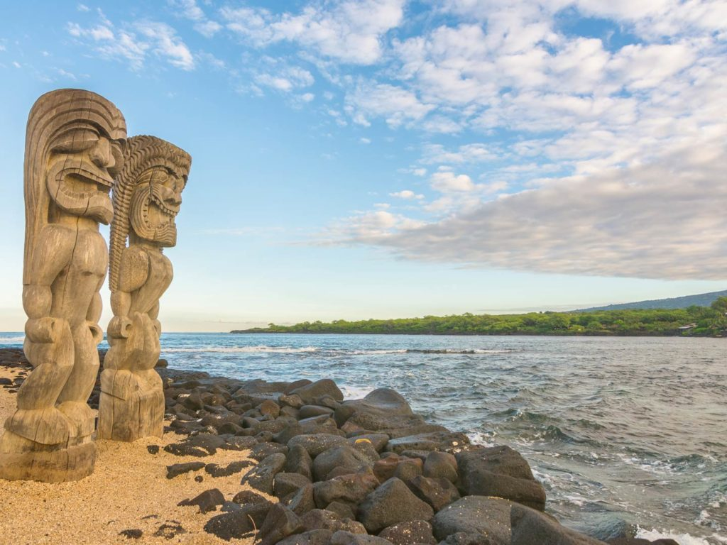 A view of the Big Island showing ancient statues in the foreground and the ocean in the background