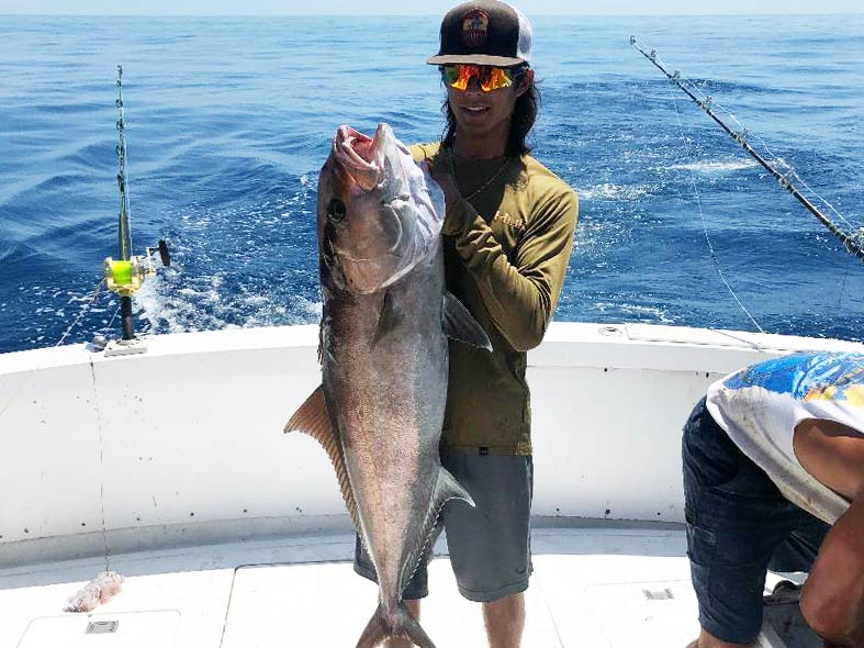 A young fisherman in a cap and sunglasses standing on a boat, holding a big Amberjack with water in the background