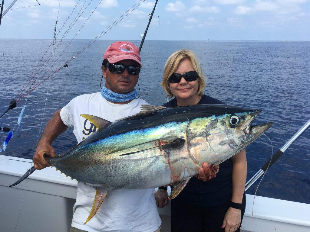 Two anglers holding a Blackfin Tuna on a fishing charter
